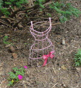 "Yes, you are seeing things right. These are little metal dresses on a hanger.  We painted them pink, added a bow, and then ""planted"" them in our garden."