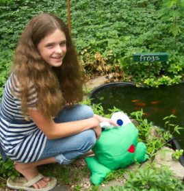 A handmade frog hanging out by the pond in front of the frog sign!