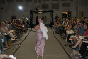 Eleven year old Fashion student walking down the runway in the jumper and white fur coat she designed and sewed.