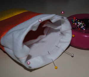 A Halloween craft that is easy to sew and handmade, featuring a candy corn drawstring bag